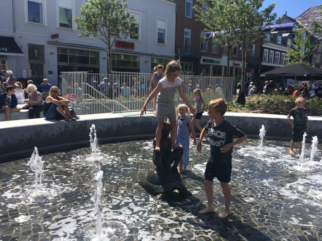 Børn der leger ved springvand